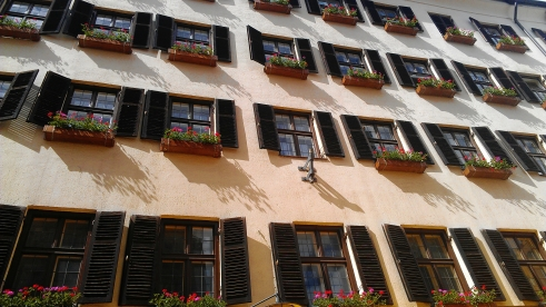 Windows with wooden shutters and pink flowers in Innsbrook, Austria.