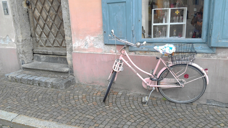 A pink bicycle along a wall in Innsbrook, Austria.